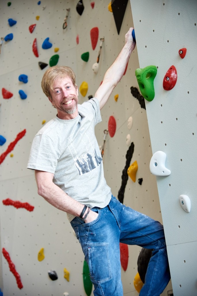 Andreas Oliver Bindhammer, the founder and CEO of eXXpozed, on a climbing wall