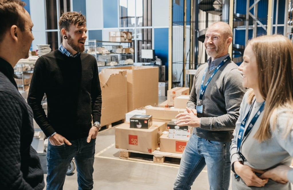Two Element Logic employees talk to two smiling customers inside a warehouse.