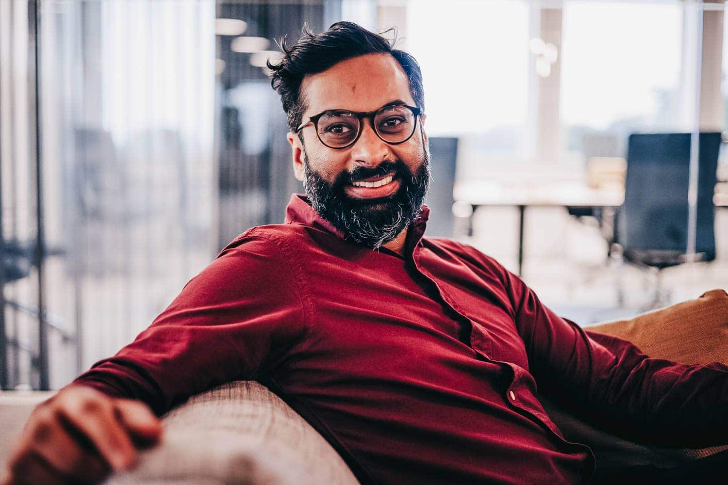 A smiling Rahman sitting on a couch looks into the camera.