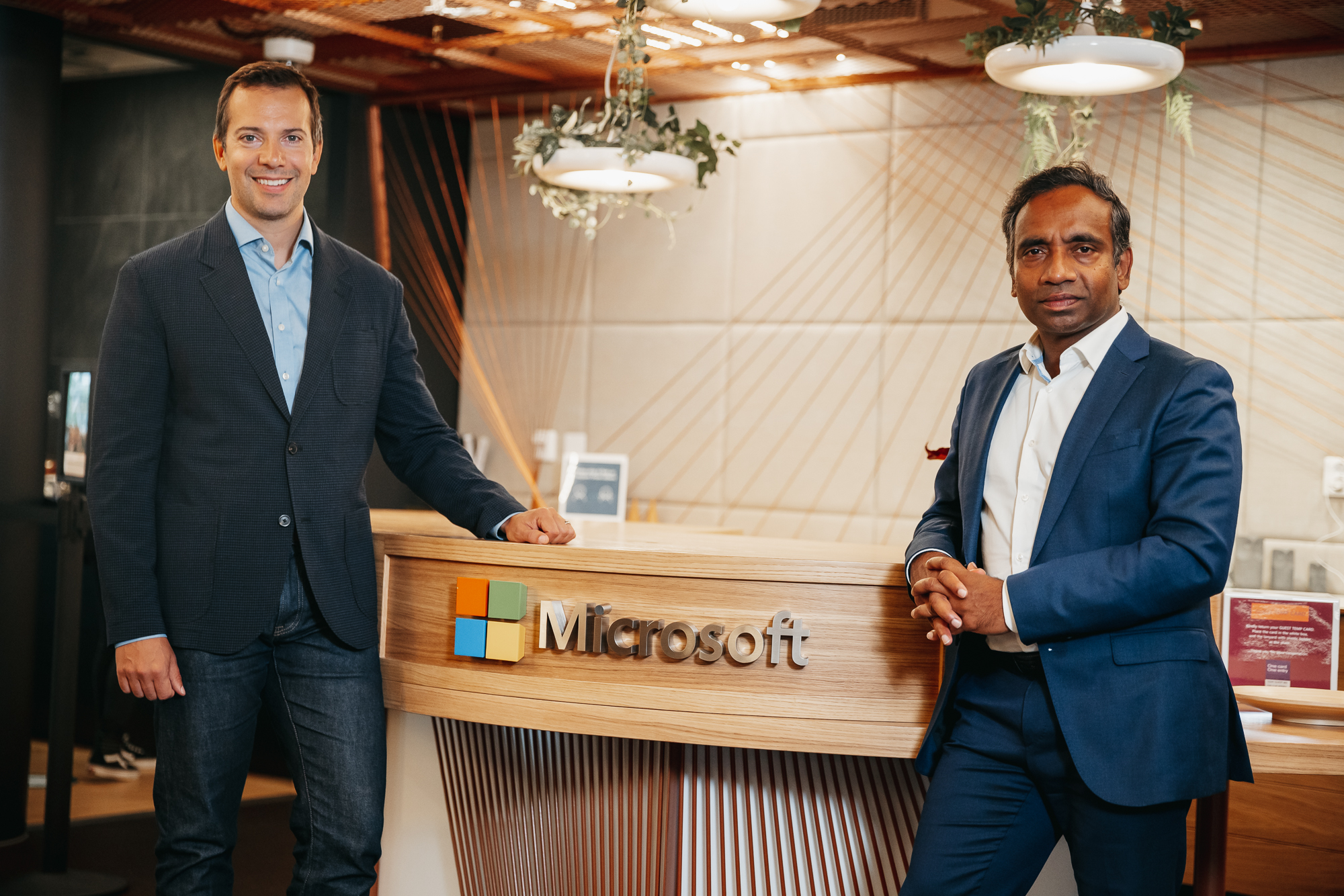 Nadarajah and Reime is smiling to the camera in front of the recepetion desk at Microsoft's office.